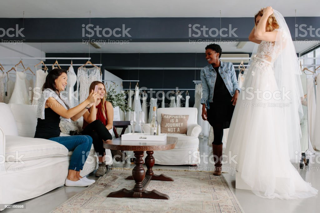 Woman trying on wedding dress in a shop with friends - foto stock