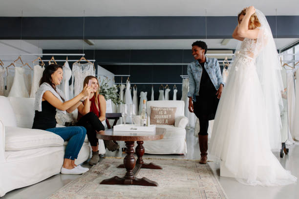 Woman trying on wedding dress in a shop with friends stock photo