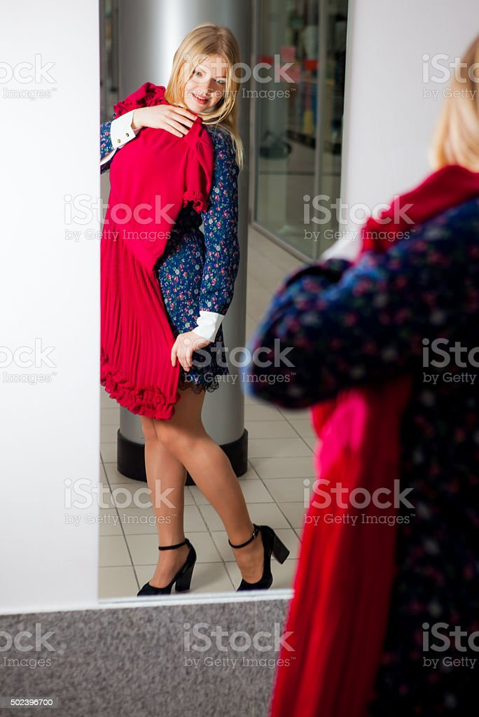 Woman trying red dress shopping for clothing stock photo