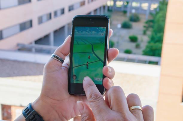 frau versucht, einen charakter mit pokemon zu fangen gehen - kostenlose onlinespiele stock-fotos und bilder