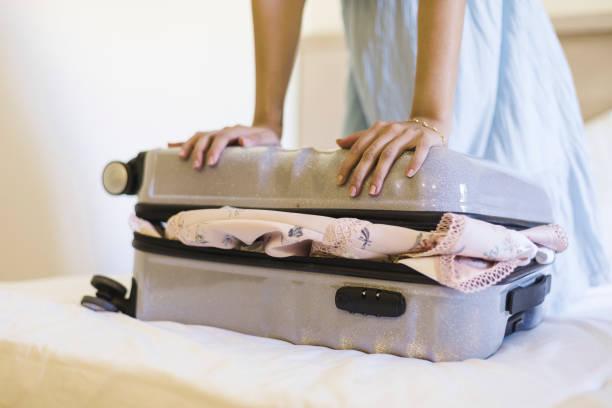 woman trying to close baggage on bed - donna valigia solitudine foto e immagini stock