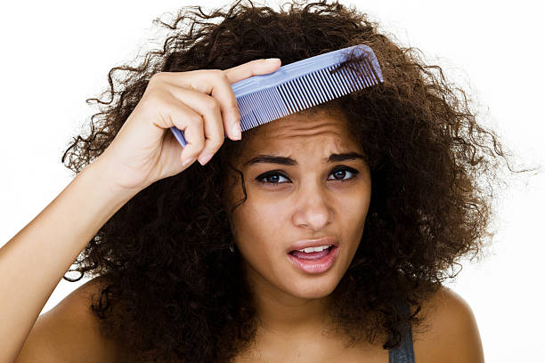 woman trying to comb her frizzy hair - messy hair stock photos and pictures