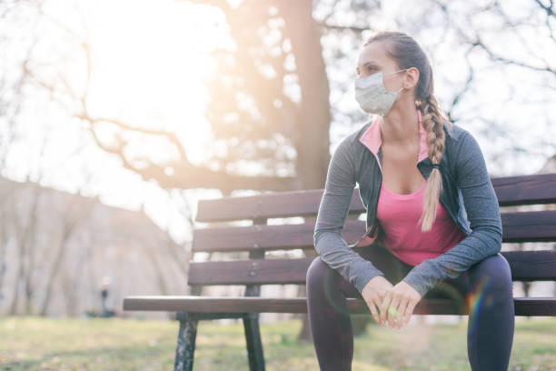 Woman trying to do sport during coronavirus crises despairing of the world stock photo