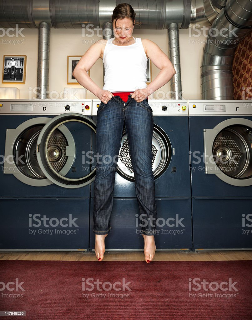 Woman trying to fit into a pair of Skinny Jeans stock photo