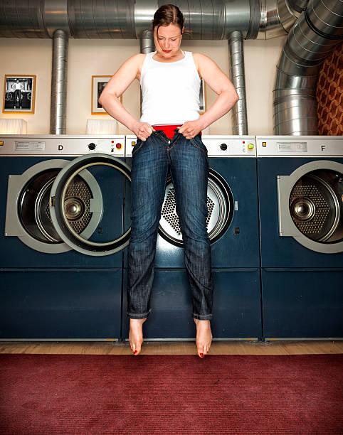 frau versucht, um in ein paar unserer skinny jeans - enganliegende jeans outfits stock-fotos und bilder