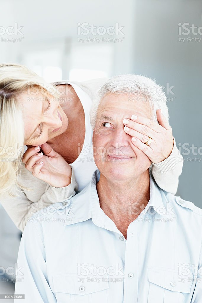 Woman trying to surprise a man by covering his eyes royalty-free stock photo