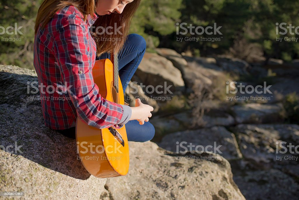 Woman tunning her Guitar stock photo