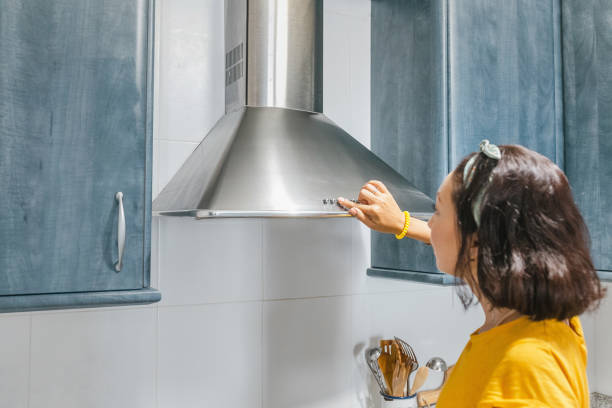Woman turn on exhaust ventilation in the kitchen Woman turn on exhaust ventilation in the kitchen vehicle hood stock pictures, royalty-free photos & images
