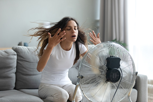 In living room without air-conditioner tired from summer heat young woman turned on floor ventilator waving her hands to cool herself, female sitting on couch suffers from unbearable too hot weather