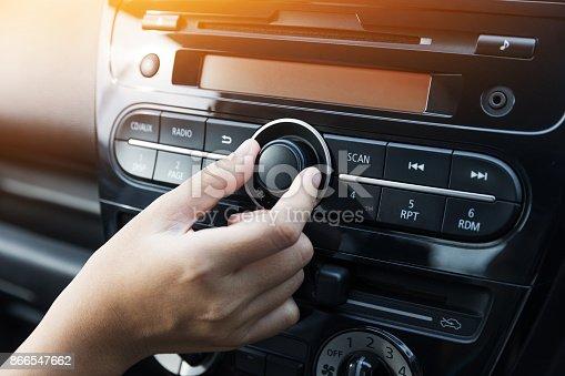 istock Woman turning button of radio in car 866547662