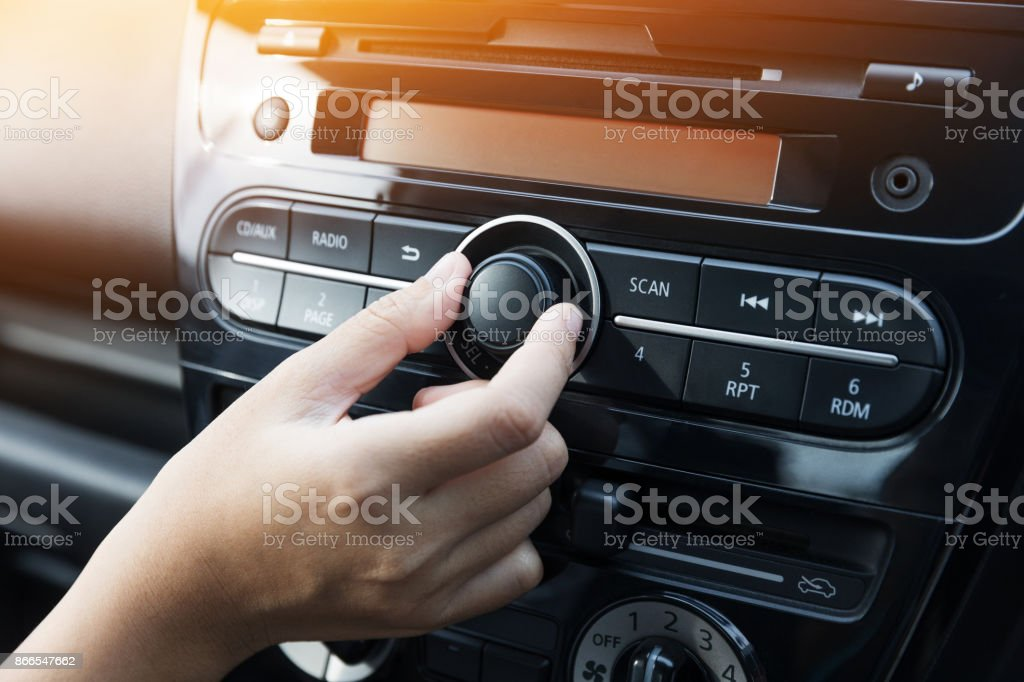 Woman turning button of radio in car stock photo