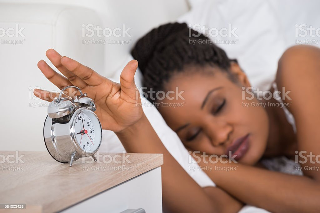 Woman Turning Off Alarm While Sleeping On Bed stock photo