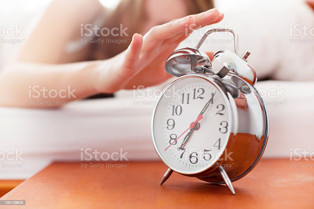 Woman turning off the alarm clock stock photo