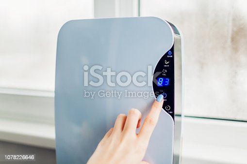 851700660 istock photo Woman turns dehumidifier on using touch panel by wet window. Humidity indicator shows high level of dampness in flat 1078226646