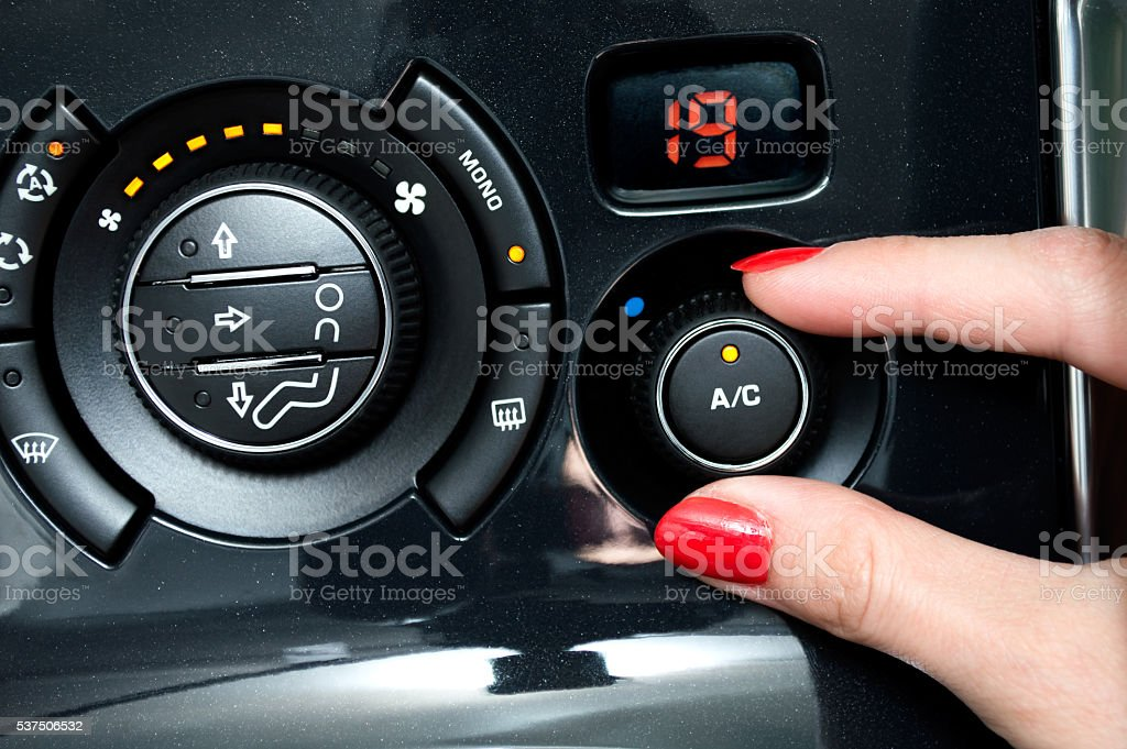 Woman turns on air conditioning in a car stock photo