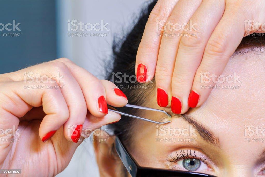Woman tweeze eyebrows stock photo