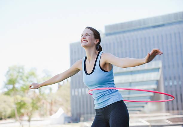 frau twirling hula-ringe - hula hoop workout stock-fotos und bilder