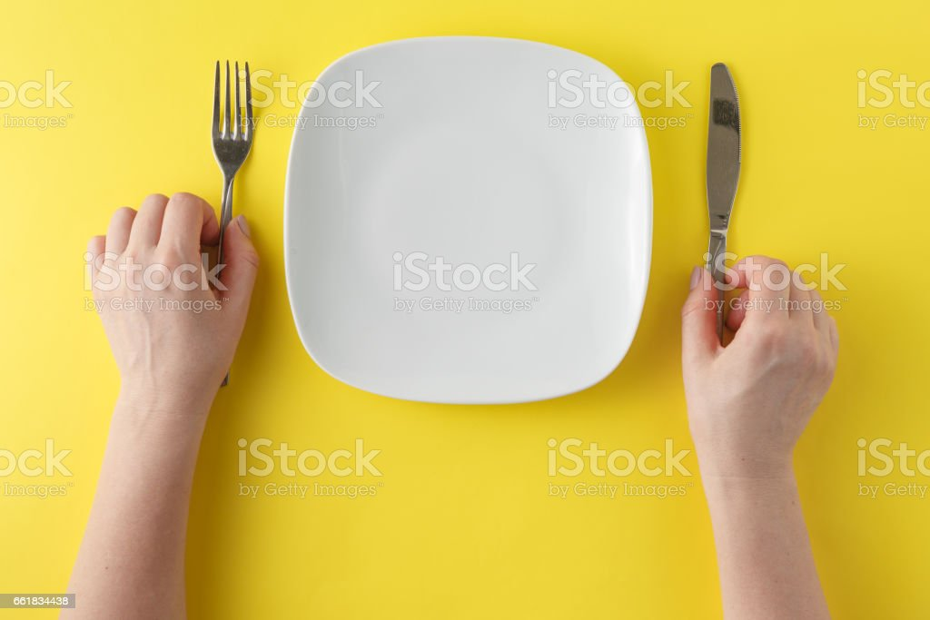 woman two hands hold a spoon and fork and white dish on yellow background – Foto