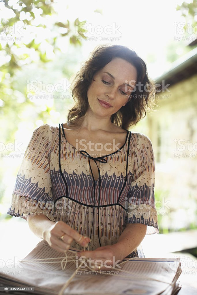 Woman tying bundle of newspaper, smiling royalty-free stock photo