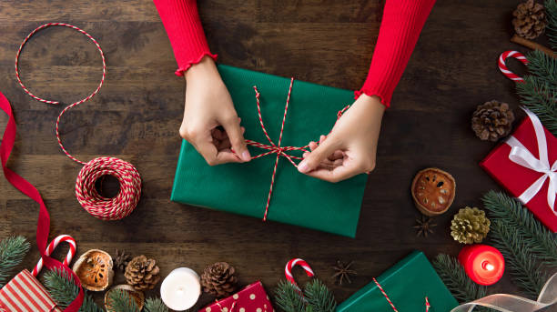 woman tying gift box in the center of christmas decorating items on a wooden table - avvolto foto e immagini stock
