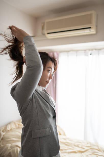 部屋に髪を結ぶ女性 - 独身の若者 ストックフォトと画像