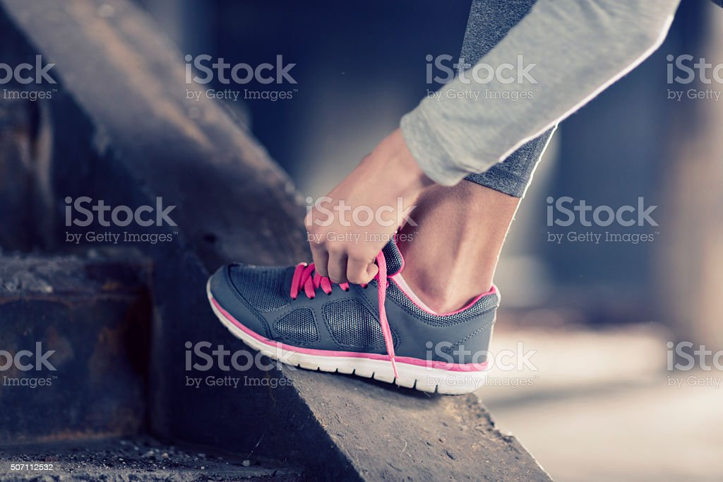 Woman tying her exercise shoes stock photo