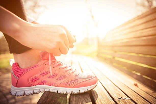 frau binden jogging-schuhe - rosa training stock-fotos und bilder