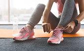 Woman tying laces preparing for training, wearing sneakers, crop, closeup
