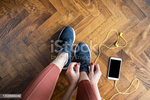 Young woman tying shoelace before workout, getting ready for jogging.