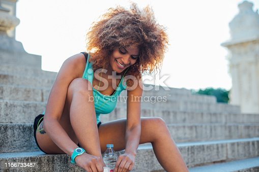Young woman resting and fixing her running shoes