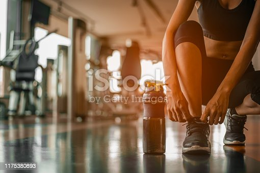 istock Woman tying shoelaces at gym.young female at gym taking a break from workout. 1175380893