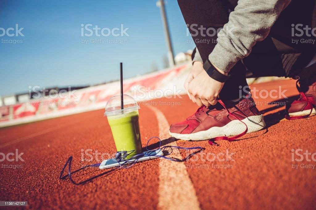 Frau bindet Schuhkarton auf Stadion - Lizenzfrei Joggerin Stock-Foto