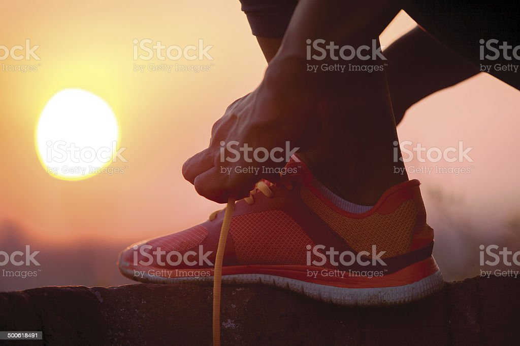 woman tying shoelaces outdoor stock photo