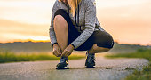 Woman tying sport shoes while jogging