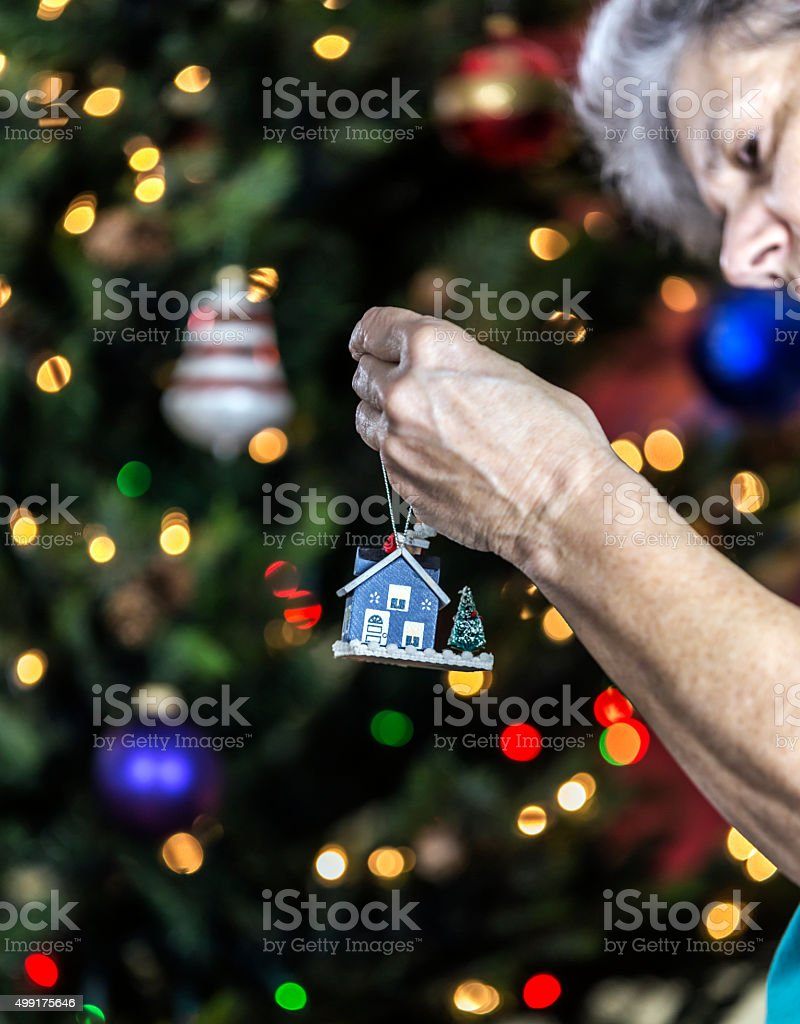 Woman Tying String To Hang Gingerbread House Christmas Tree