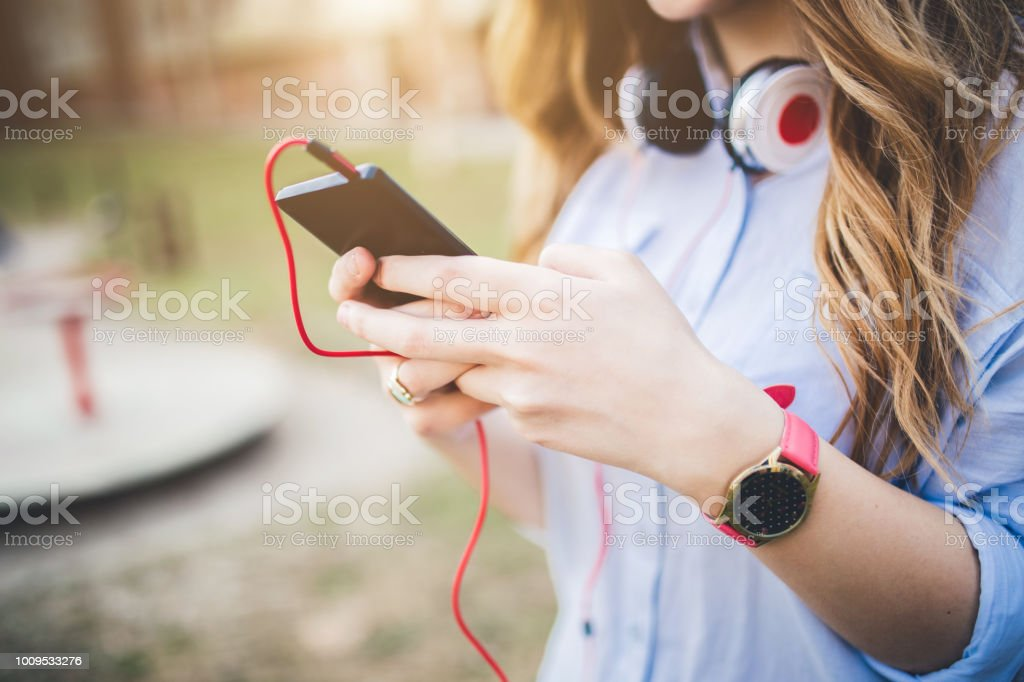 Hand of young caucasian woman typing a message on mobile phone. Close...