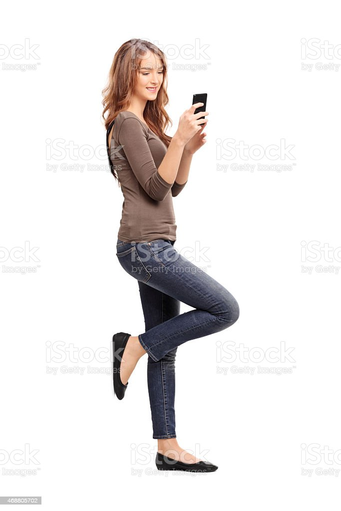 Woman typing a text message on her cell phone stock photo