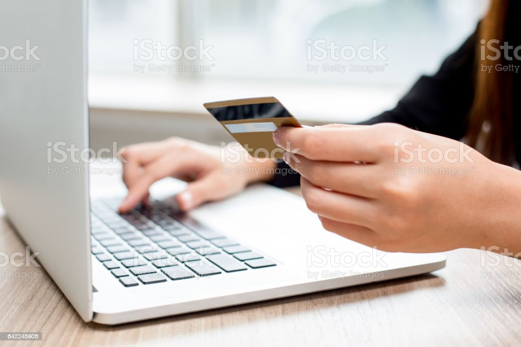Woman typing credit card information on laptop stock photo