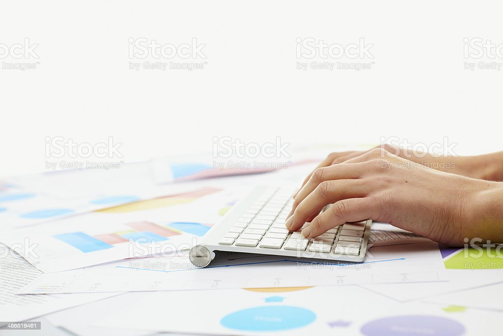 Woman typing on keybord with charts around her stock photo