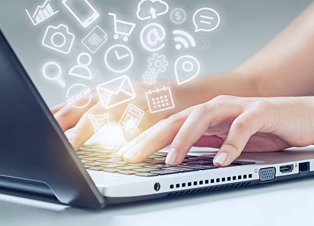 woman typing on laptop and media icons fly off - comunication icon stock photos and pictures