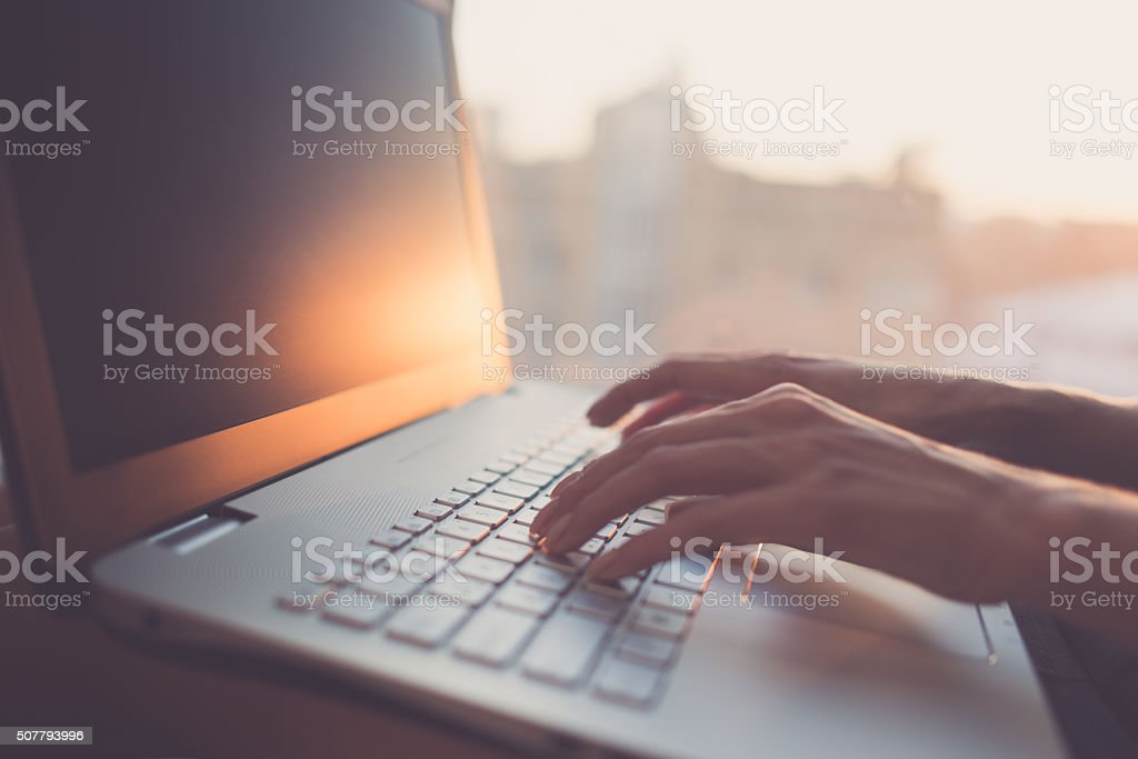 Woman typing on laptop at workplace working in home office stock photo