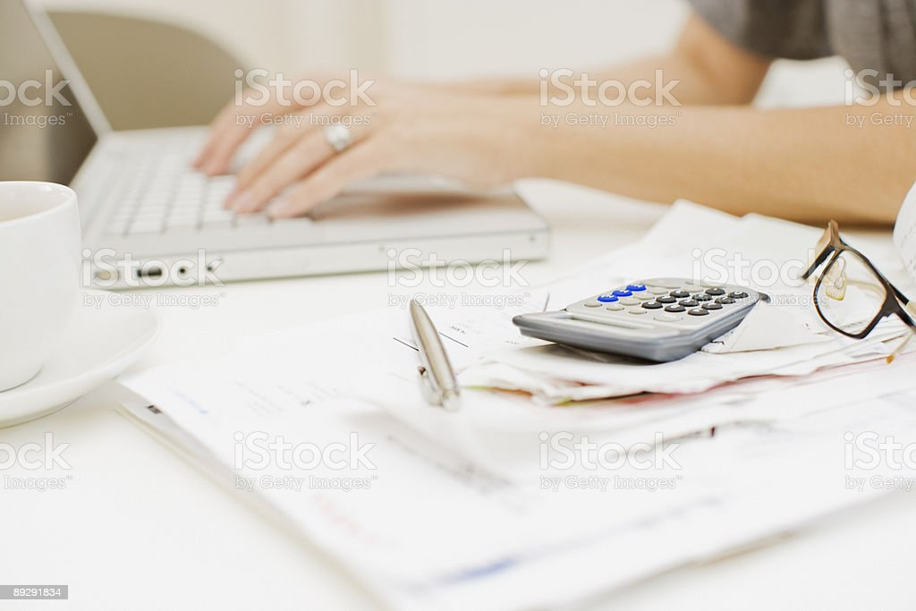 Woman typing on laptop near bills and calculator stock photo
