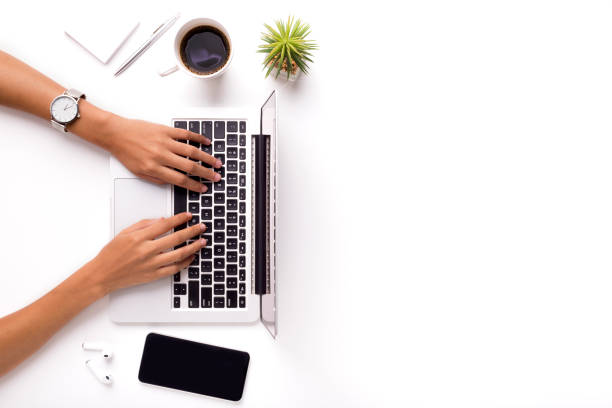 Woman typing on laptop on clean white office table with plant Woman typing on laptop on clean white office table with plant and cup of coffee, copy space business laptop stock pictures, royalty-free photos & images