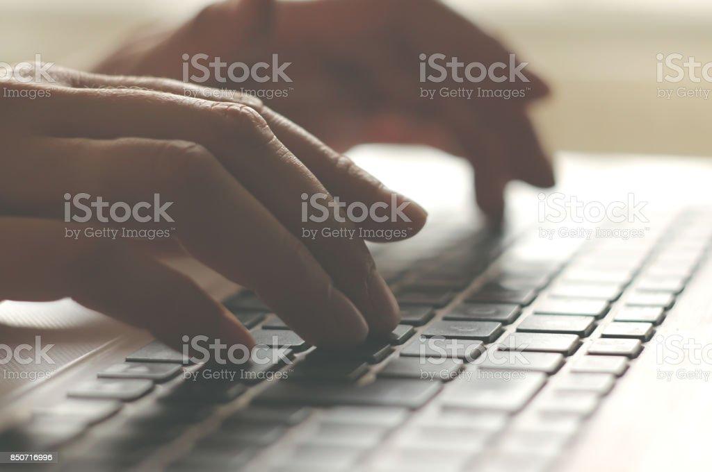 Woman typing on laptop stock photo
