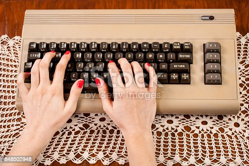 Woman finger press button on old computer keyboard on wooden and doily desk. Retro and Vintage