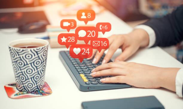 Frau auf drahtlose Tastatur und Benachrichtigung Symbole des sozialen Netzwerks fliegen über Tastatur eingeben – Foto