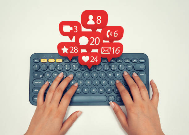 Frau auf drahtlose Tastatur und Benachrichtigungen Symbole des sozialen Netzwerks fliegen über Tastatur eingeben – Foto