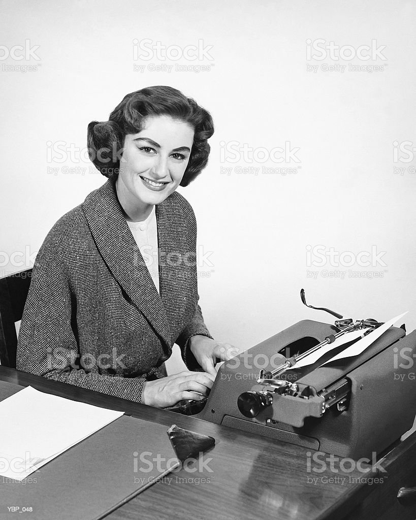 Woman typing, posing and smiling royalty-free stock photo
