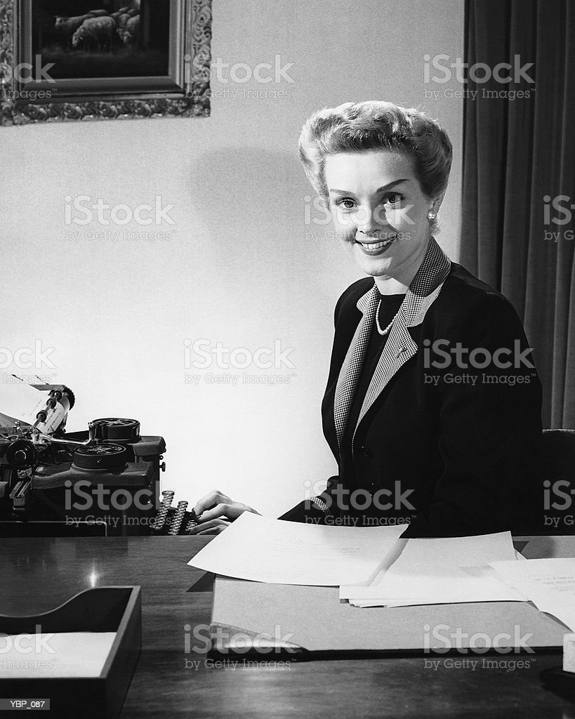 Woman typing, posing and smiling royalty free stockfoto