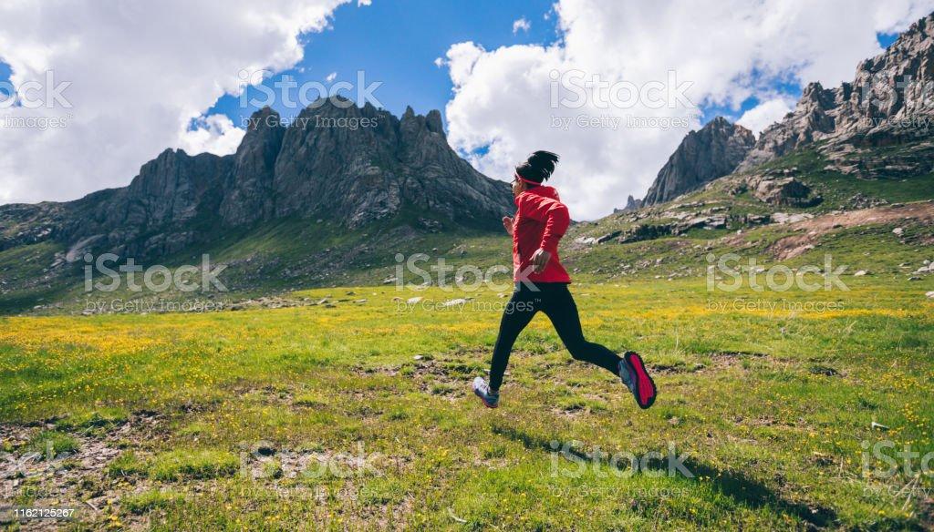 Frau Ultra-Marathon-Trailrunner läuft auf schönen Bergen - Lizenzfrei Abenteuer Stock-Foto
